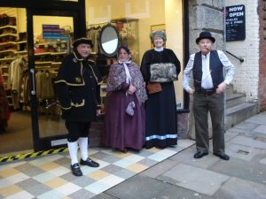 Derek Town Crier, Jill in burgundy Victorian, Coral in black Edwardian and Tony in wiastcoat and bowler hat