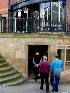 People entering the doorway of the building on Mealhouse Brow