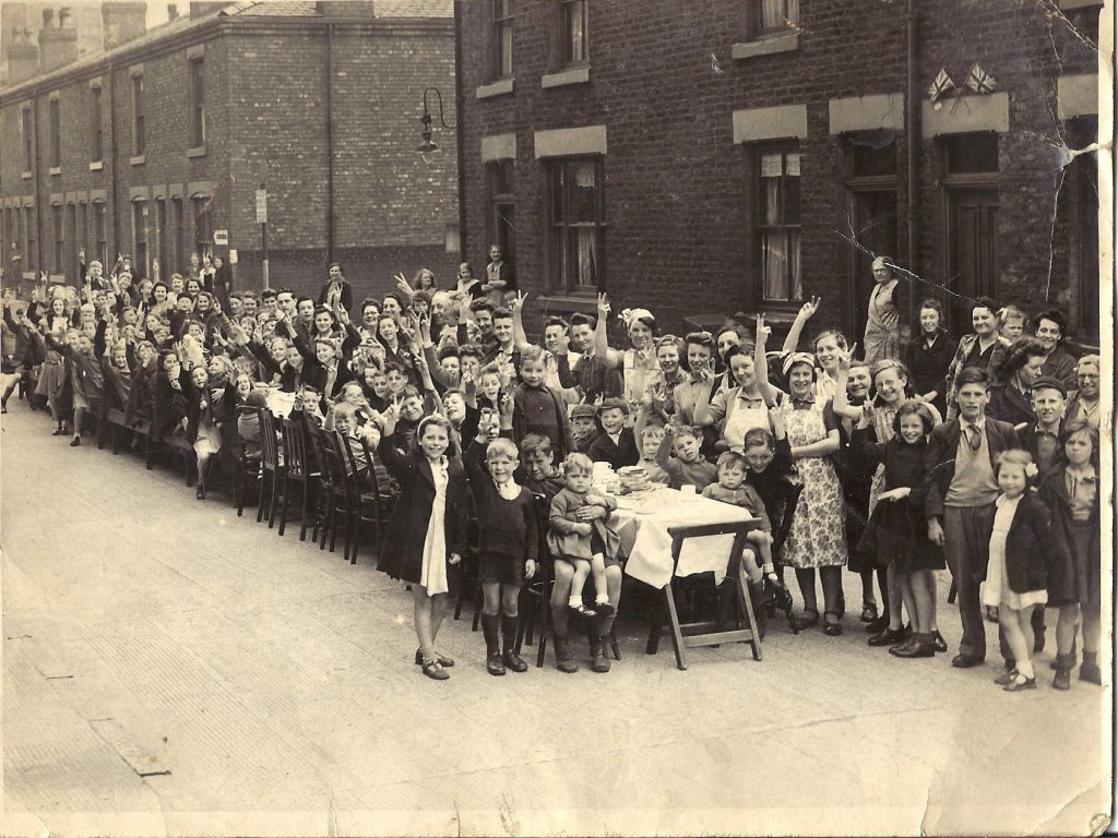 Crowds sat at a very long table line the terraced street cheering and showing the Victory sign.