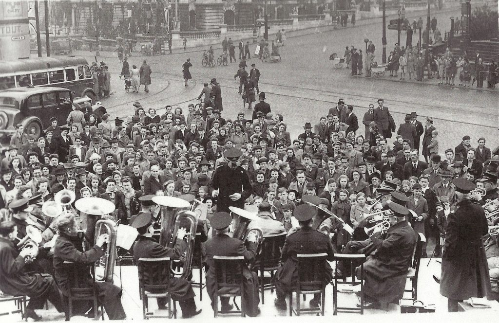 Crowds gather in front of a brass band at Stockport's War Memorial on the corner of Greek St and Wellington Road