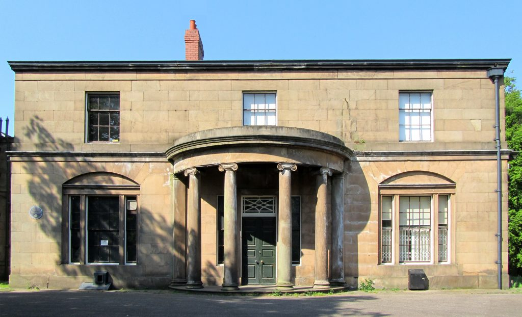 View from directly in front of Woodbank Hall, Stockport. Four columns hold up a semi circular porch on the regency stone house