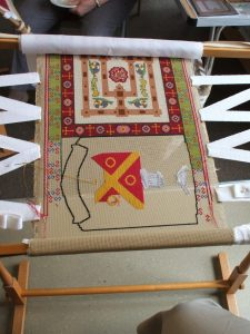 Partially completed cross stich work on a frame