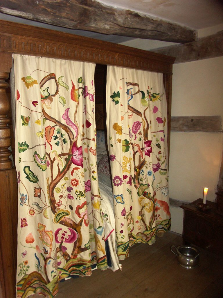 Side view of two colourful bed hangings in situ